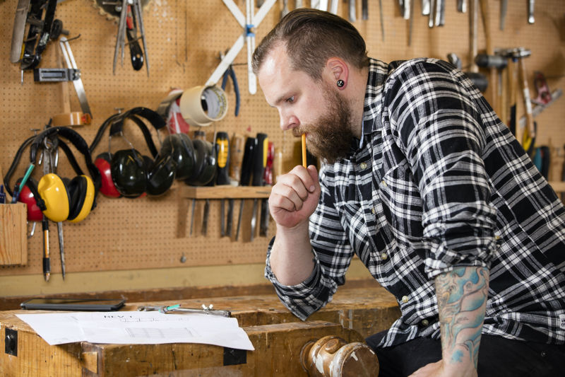 Adult craftsman sits and looks at plans in a work shop for wood work and construction. Carpenter designs and prepares new work.