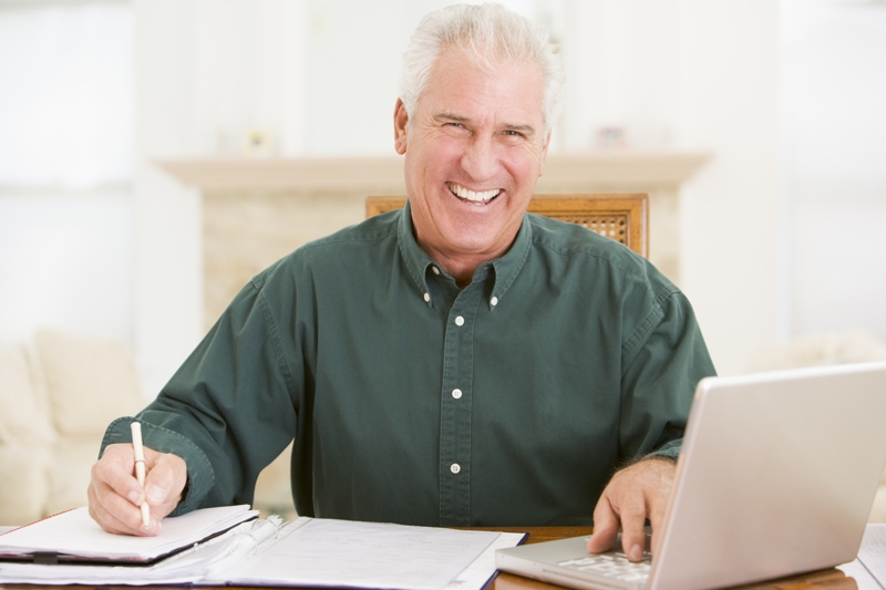 Man in dining room with laptop and paperwork smiling