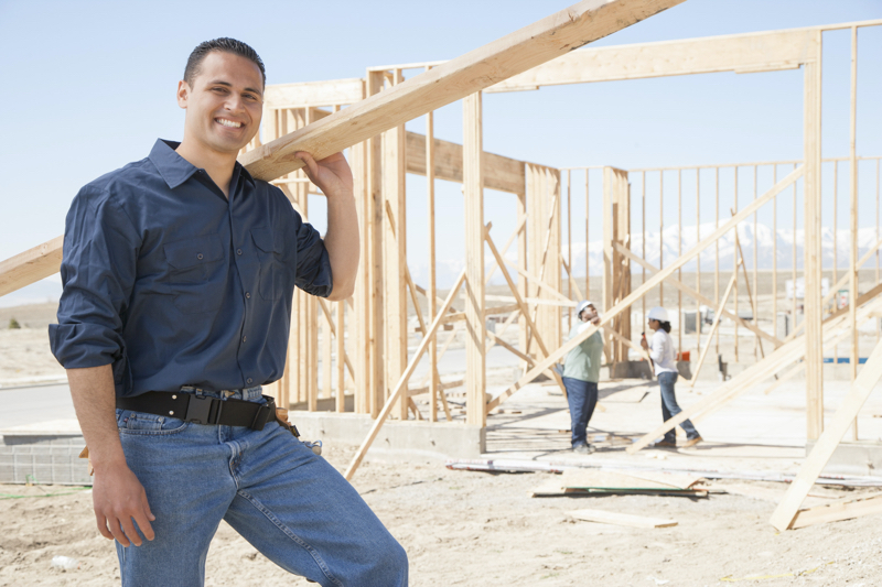 Builder on a worksite, constructing a home without safety equipment.